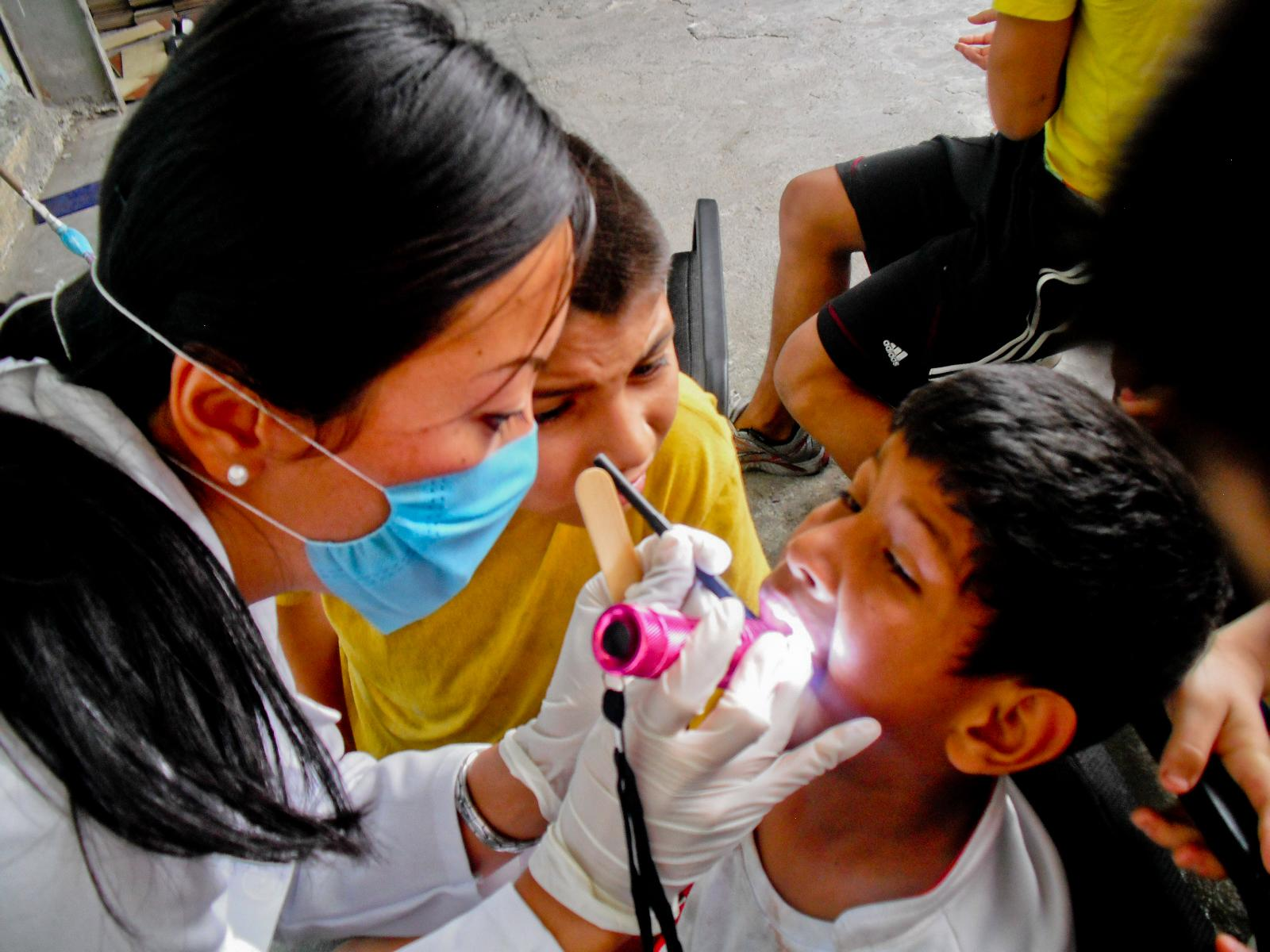 A Projects Abroad intern examines a young local boy during a medical outreach on her Dentistry internship in Mexico.